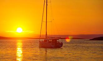 Rot glühend versinkt die Sonne über dem Meer. Im Hintergrund die Inseln der Kvarner Bucht